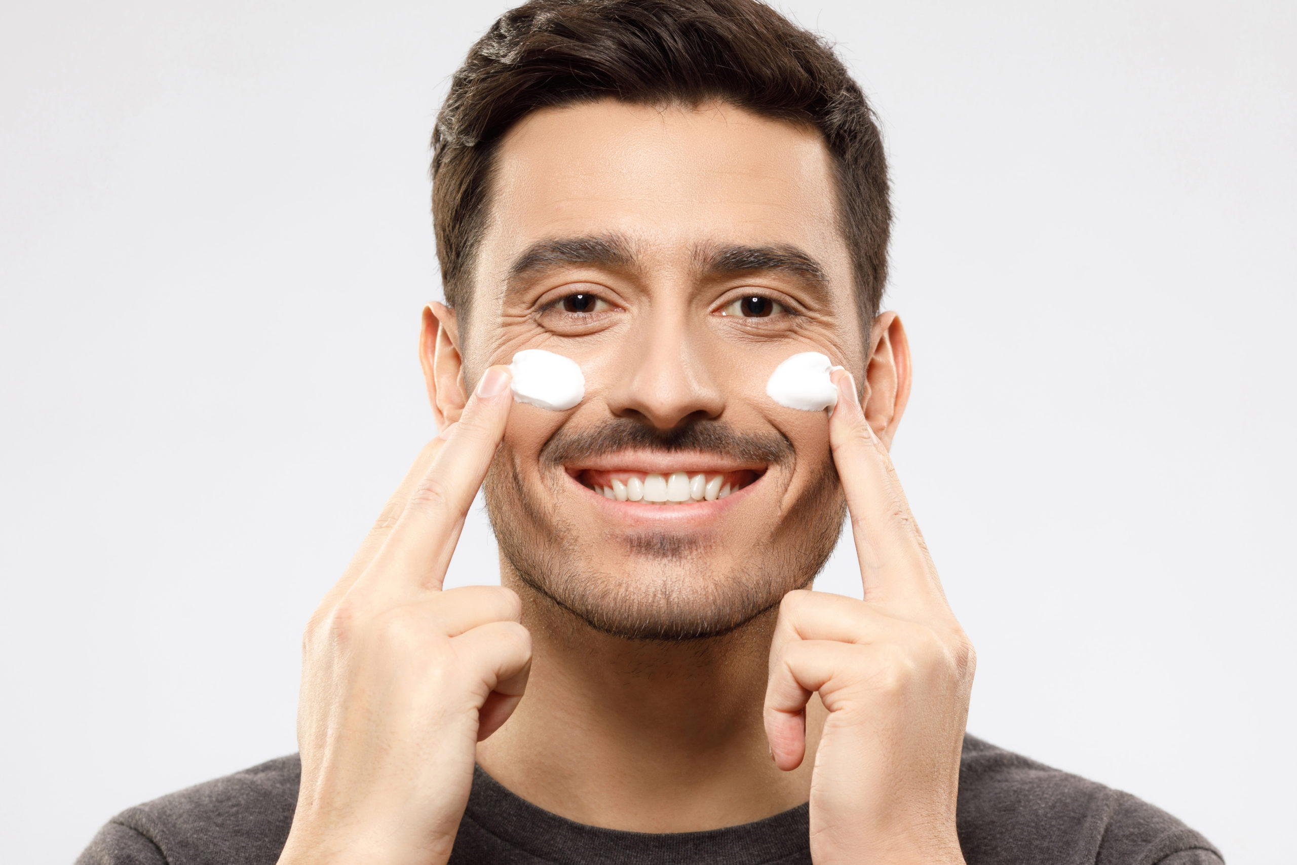 Handsome young man looking at camera, touching cheeks with fingers, applying face cream, feeling satisfied with beauty routine, isolated on gray background. Skin care men