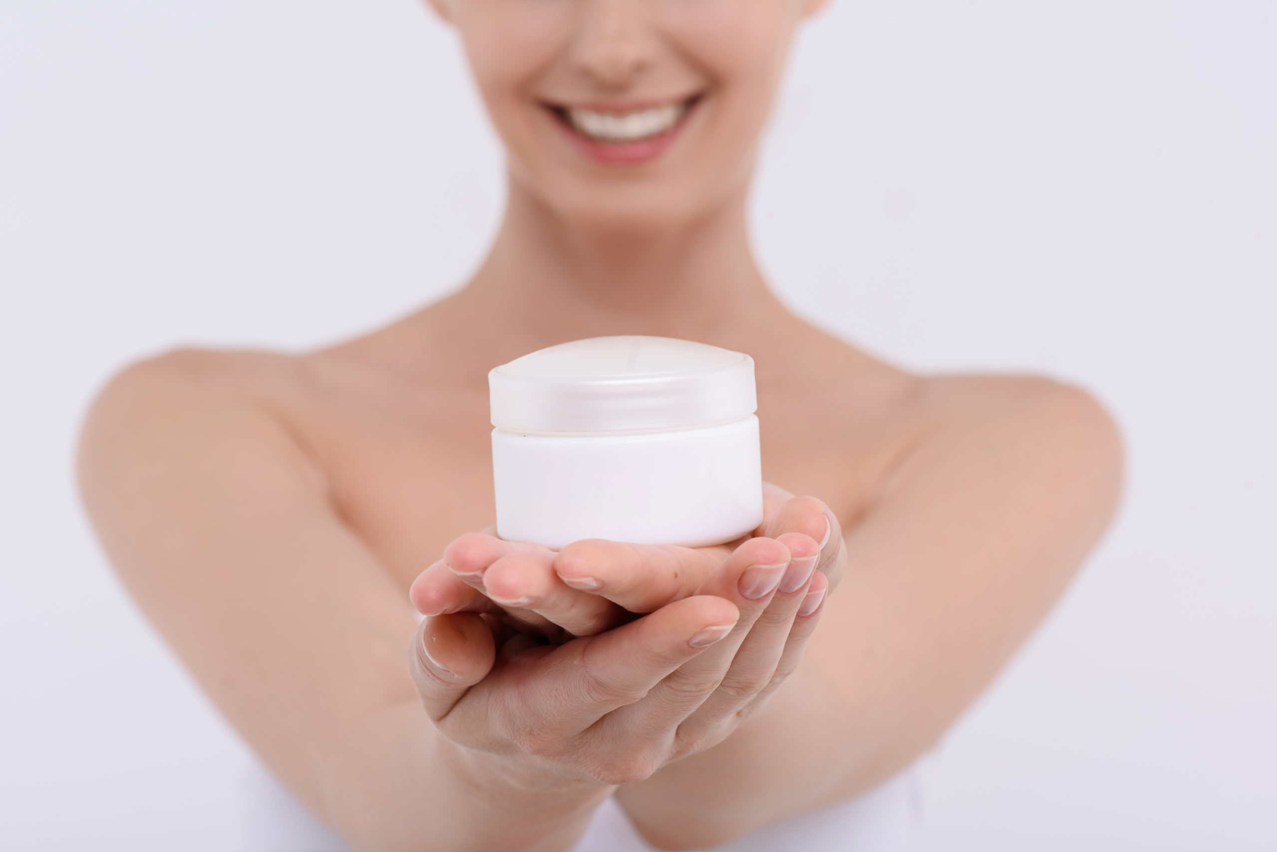 This cream will make your face perfect. Joyful young woman is showing cream can to camera. She is standing and smiling. Isolated
