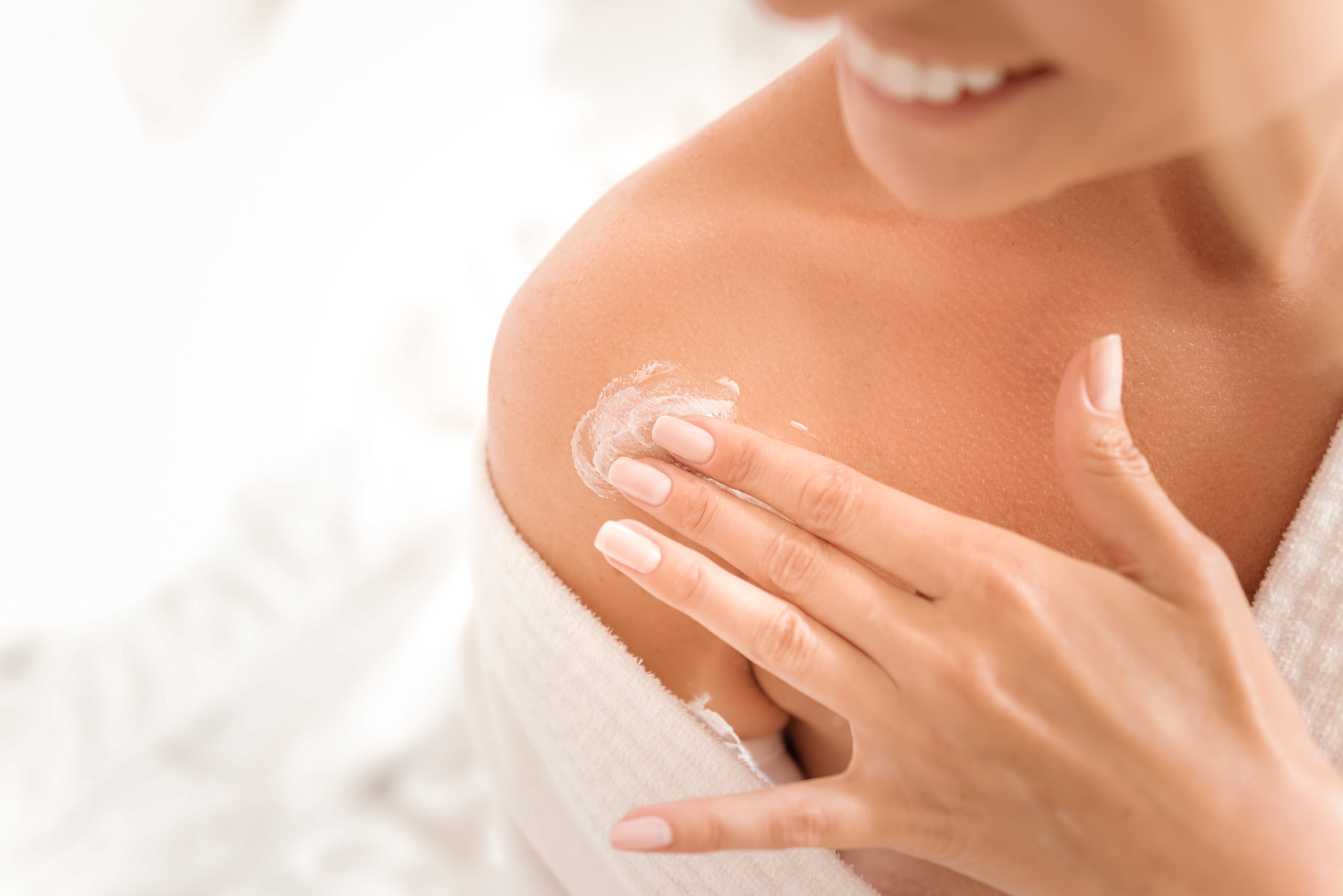 Natural beauty. Close up of female shoulder with a little of moisturizing cream being applied on it